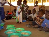 Vol verwachting kijken de kindertjes toe tot ze hun bordje maispap krijgen