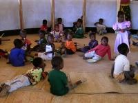 Verspreid over de grond genieten de kinderen van hun maispap